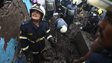 Pelastushenkilöstö tutkii tuhoisan maanvyöryn jälkiä. Kypäräpäinen mies katselee yläviistoon toisen kaivaessa.