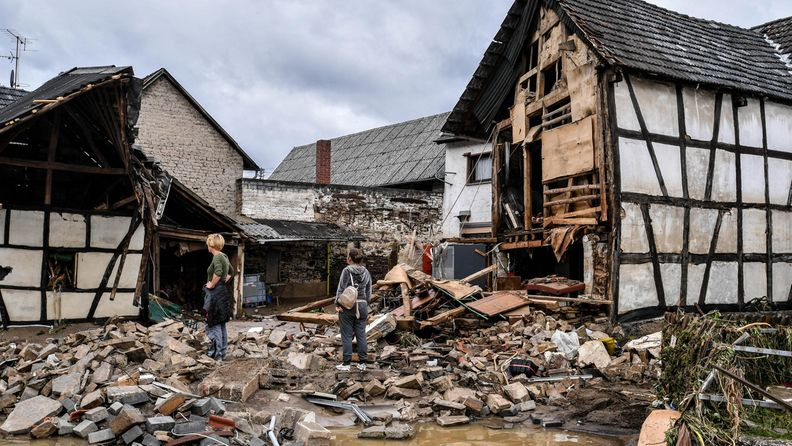 Ihmiset pällistelevät tulvassa tuhoutuneiden talojen keskellä.