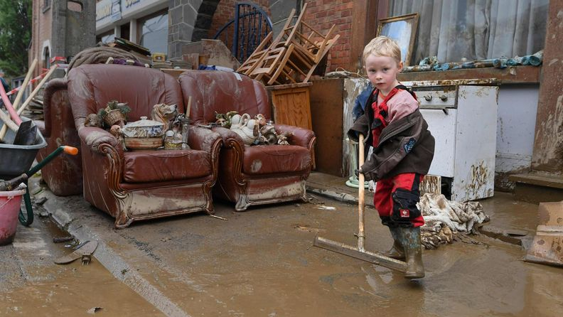 Lapsi auttaa puhdistustöissä tulvan jälkeen Saksassa.