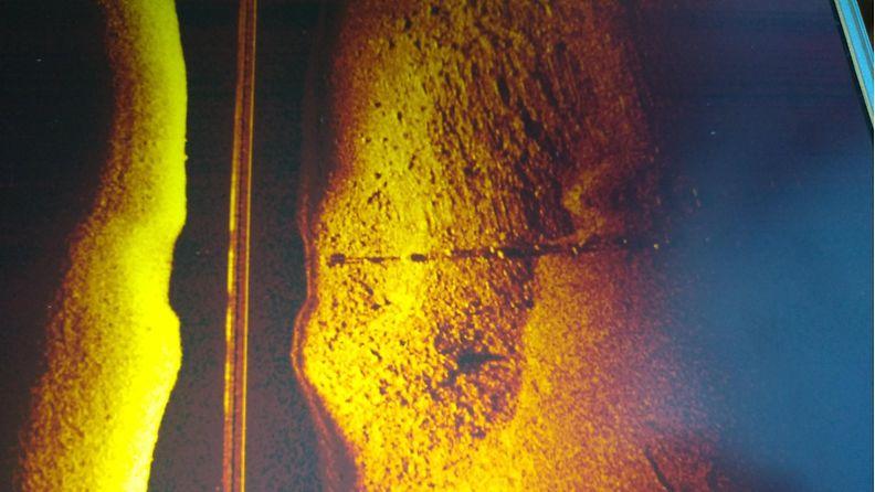 Esimerkkikuva viistokaikuluotaimen tuottamasta kuvasta. Kuva ei liity Jussi Peltolan tapaukseen. Kuvassa pohjaan painotettu vesijohto kivikkoisella pohjalla.