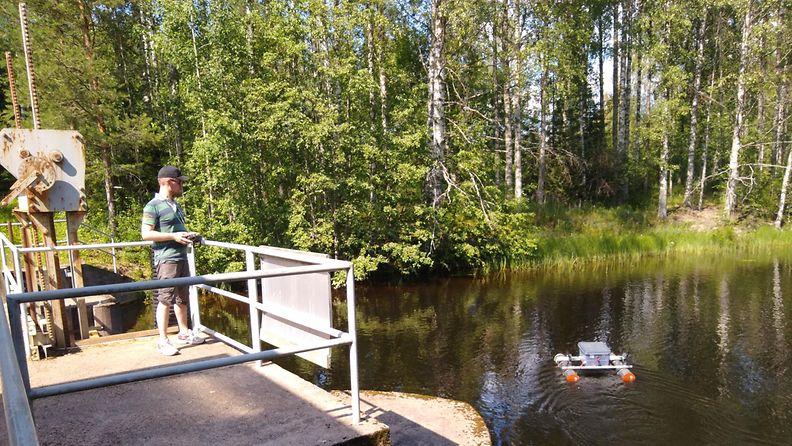 Antti ohjaa venettä, jossa viistokaikuluotain. Kuva otettu ensimmäisellä etsintäreissulla 5.7.2021.