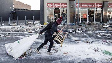 Pipopäinen mies raahaa kadulla säkkiä täynnä mahdollisesti ryöstettyä tavaraa, tuoli toisessa kädessään.