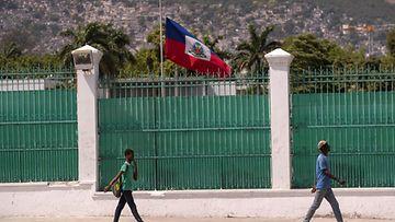 Haitilaiset kävelevät korkean aidan edustalla, jonka takana liehuu valtion lippu puolisalossa.