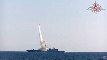 Venäläinen sotalaita testaa ohjusta, joka nousee savupatsaan saattelemana mereltä.