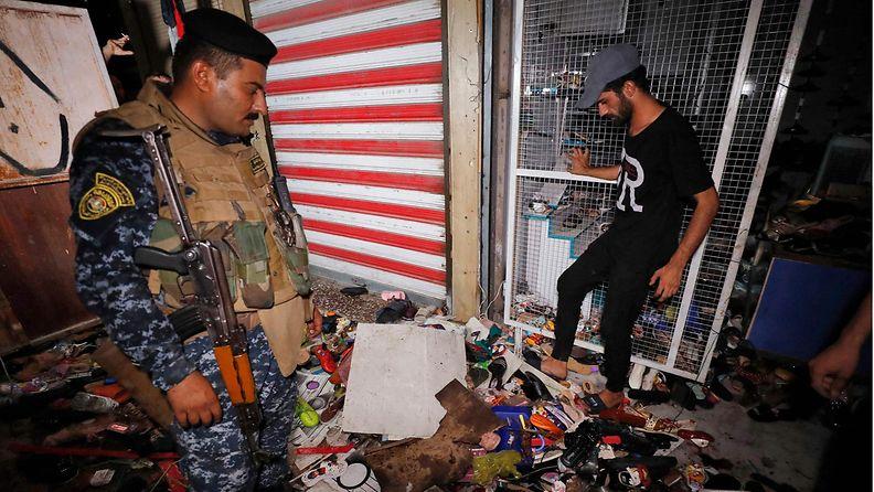 Irakilaiset tutkivat pommi-iskun jälkiä.
