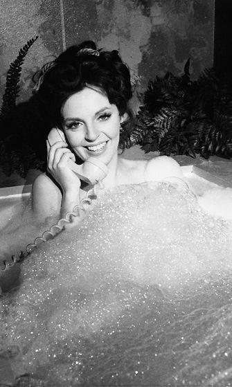 Nainen kylvyssä puhelimen kanssa