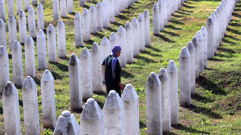 Huivipäinen nainen kävelee hautakivien lomassa.