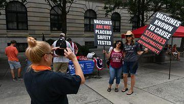 Kaksi naista poseeraavat kylttien kanssa rokotevastaisten mielenosoituksessa.