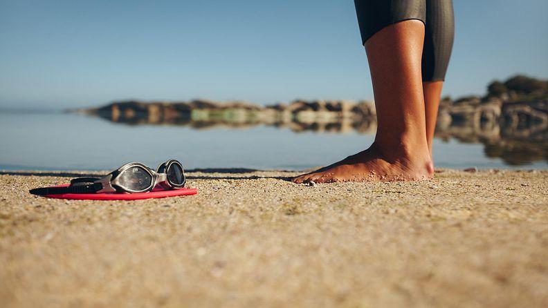 nainen rannalla märkäpuvussa