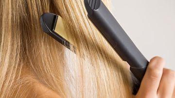 nainen suoristaa hiuksiaan