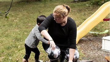 Adoptioäiti Anna Juustovaara ja Thaimaasta adoptoitu Hugo pihaleikeissä Porvoossa