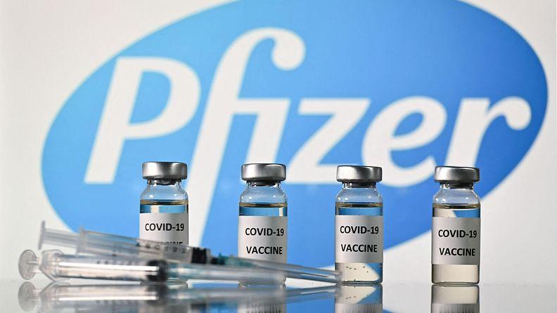Covid-19 rokoteputeleita rivissä ja ruiskut lepäävät pöydällä edessä. Kimmeltävien purkkien taustalla paistaa Pfizerin logo.