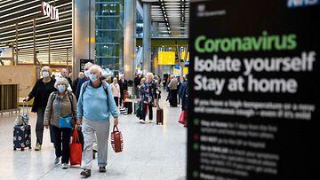 Ikäihmiset tallustavat lentokentällä kassit kourassa. Oikealla näkyy kyltti, jossa kehotetaan eristäytymään.