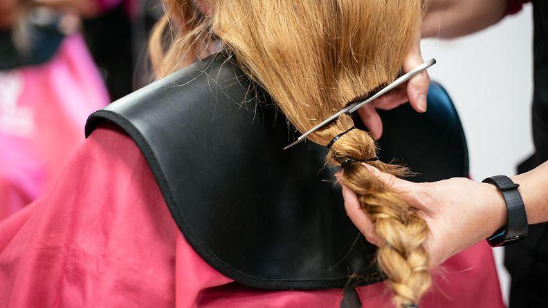 Kampaaja leikkaa pitkät hiukset