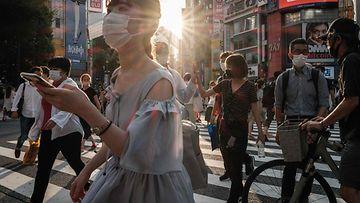Ihmisiä kasvomaskit kasvoillaan ylittävät tietä Tokiossa, Japanissa 28. heinäkuuta.