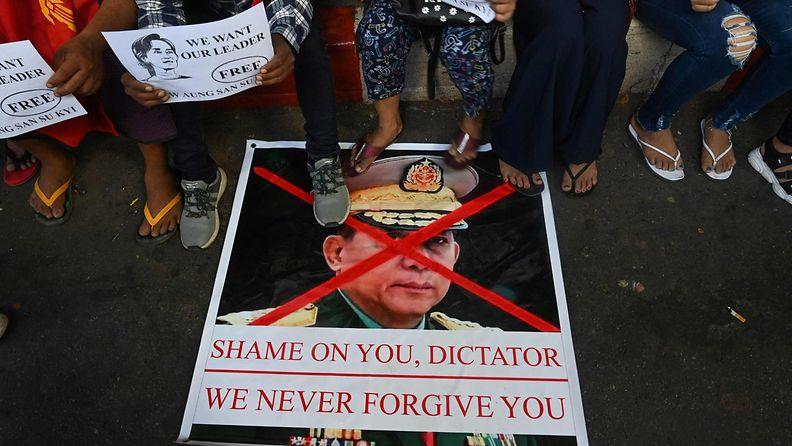 Mielenosoittajat seisovat sotilasjunttan johtajaa vastustavan kyltin päällä.