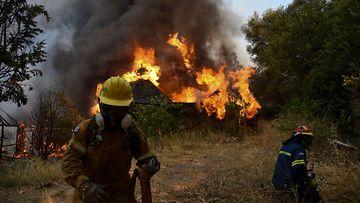 Savupastas nousee ilmiliekeissä olevasta rakennuksesta palomiesten sammuttaessa.