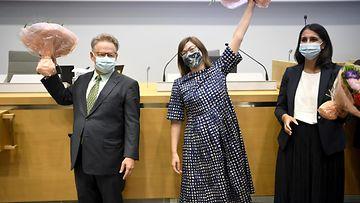 Helsingin kaupunginvaltuuston valitsemat pormestari ja apulaispormestarit tuulettavat kukkakimput käsissään ja maskit kasvoillaan.
