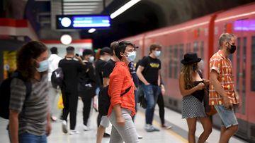 Ihmiset talsivat metroon maskit kasvoillaan.