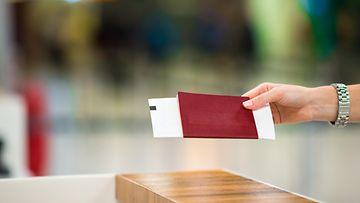 nainen lentokentällä passin kanssa