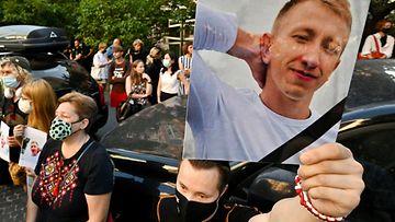 Mielenosoittaja pitää kädessään suurta kuvaa Vitaly Shishovista mielenosoituksessa. Taustalla seisoo muita mielenosoittajia.