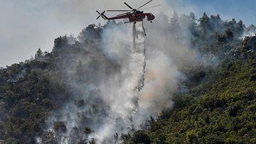 Helikopteri lorauttaa annoksen vettä savuavaan metsään.
