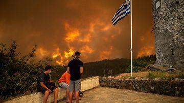 Kundit ihmettelee palon keltaiseksi värjäämää maisemaa Kreikan lipun liehuessa salossa.
