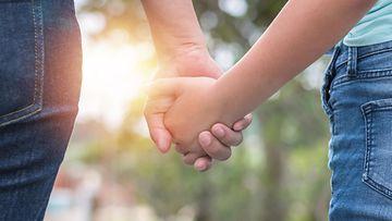 äiti ja teini-ikäinen tytär käsi kädessä