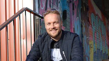 Sami Minkkinen istuu portailla ja katsoo kameraan hymyillen.
