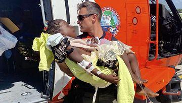 Yhdysvaltain rannikkovartija kantaa loukkaantunutta lasta pelastuskopteriin.