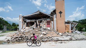 Lapsi pyöräilee sortuneen kirkon edestä.
