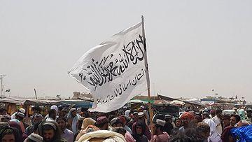 Talebanin lippu liehuu väkijoukon keskellä.