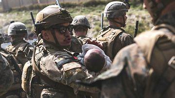 Yhdysvaltalaissotilas kantoi lasta sylissään Kabulin lentokentällä 20. elokuuta.