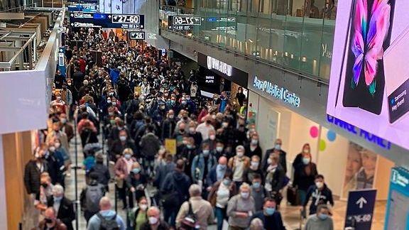 Ihmismassa jonottaa ruuhkassa Helsinki-Vantaan lentokentällä.