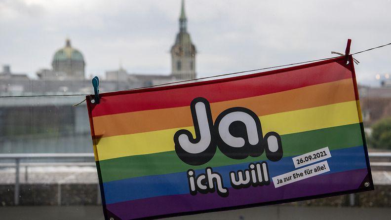 Sateenkaaren väreissä oleva lippu, jossa lukee Ja, ich will.