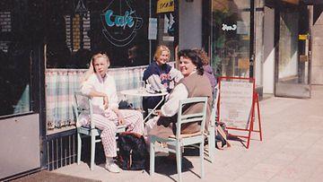 Heli (tumma edessä) seurustelee asiakkaiden kanssa Cafe' Avec Toi -kahvilansa edustalla.