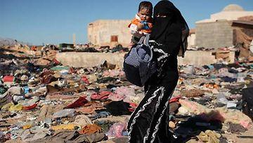 Nainen ja lapsi pakenevat Libyasta Tunisian puolelle.