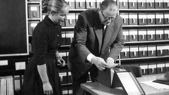 1962: Suomen Akatemian jäsen, professori Kustaa Vilkuna tarkastelee assistenttinsa kanssa paikannimiarkiston kortteja. Kuva on säästöpankkien akateemikkosarjan elokuvasta. LEHTIKUVA / HS
