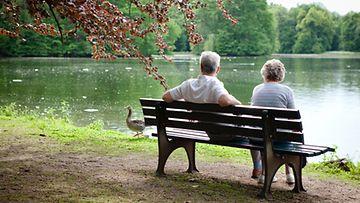 Vanha pariskunta istuskelee lammen rannalla.