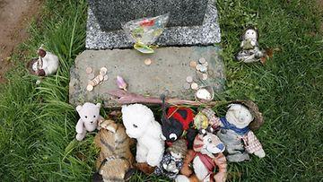 Titanicin haaksirikossa kuolleen tuntemattoman lapsen hautakivi on koristeltu leluin.
