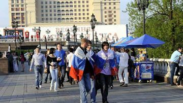 Paikallisia Venäjän lippujen kanssa Moskovan keskusaukiolla.
